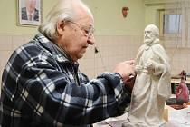 Sochař Jindřich Roubíček dokončuje sochu svatého Jakuba.
