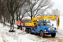 Autojeřáb vyprošťoval na silnici do Božanova z příkopu zapadlý vůz silničářů, kteří silnici za silného větru protahovali.