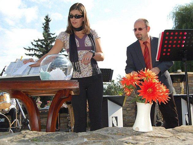 Iveta Josífková, zpěvačka Big Bandu Dvorský, losuje za asistence Milana Horkého, ředitele Muzea Boženy Němcové, šťastlivce, který se zúčastnil soutěže o Královnu jiřin a dostal věcnou cenu.