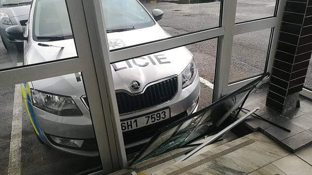 Auto narazilo do policejního vozu, který prorazil skleněnou výplň vestibulu budovy.