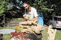 ŘEZBÁŘ JAN RÁZEK při práci, závěrečný vzhled sochy dotváří pomocí dláta. Jeho hlavním nástrojem je ale motorová pila.