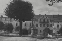 Pohled na Jižní část náměstí v Olešnici v Orlických horách. Tato část se téměř nezměnila, kašna zde stojí dodnes. Fotografie pochází z roku 1935.