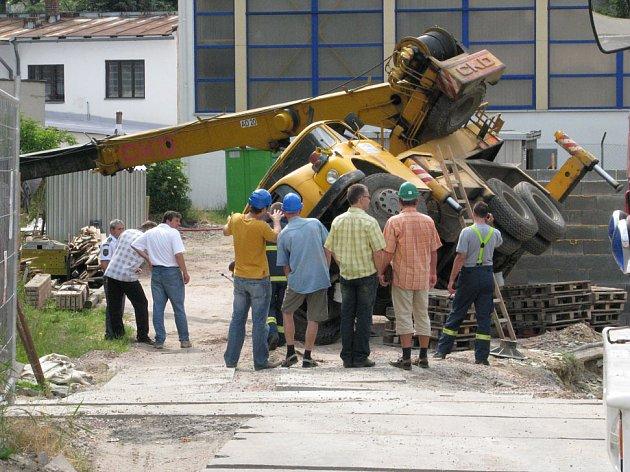 Autojeřáb se převrátil na bok a musel být vyproštěn druhým autojeřábem.
