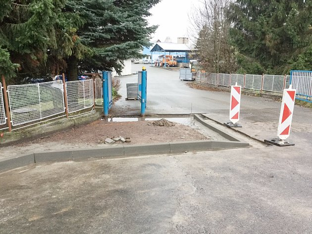 Chodník, který zasahuje do výjezdu z areálu v Lukavici, ve kterém sídlí několik firem, právě staví obec.
