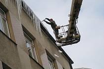 Pracovníci soukromé firmy strhávají největší rampouchy z budovy rychnovského Městského úřadu.