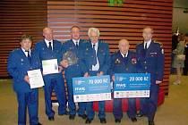 Na snímku uprostřed vlevo Deštenští přebírají ocenění za 1. místo v kategorii jednotky oblasti východních Čech včetně exkluzivní skleněné přilby zhotovené v nižborských sklárnách.