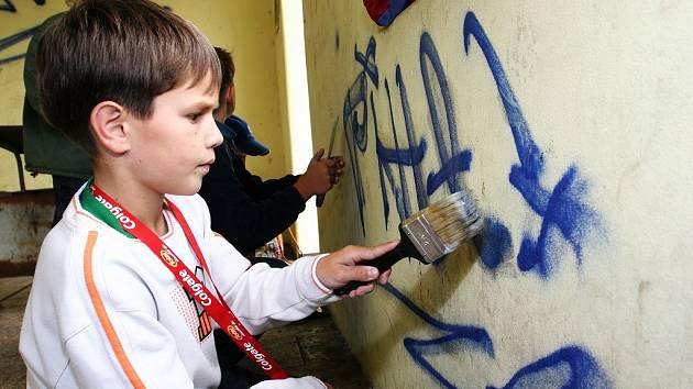 Děti z Častolovic zbavují místní vlakovou zastávku sprejerských výtvorů.