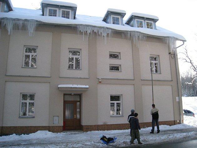 Několikametrové rampouchy, které hrozily pádem u vchodu do horské chaty v Novem Hrádku, odstraňuje Jiří Novotný. Po pádu na zem se led rozlétl v okruhu několika metrů.