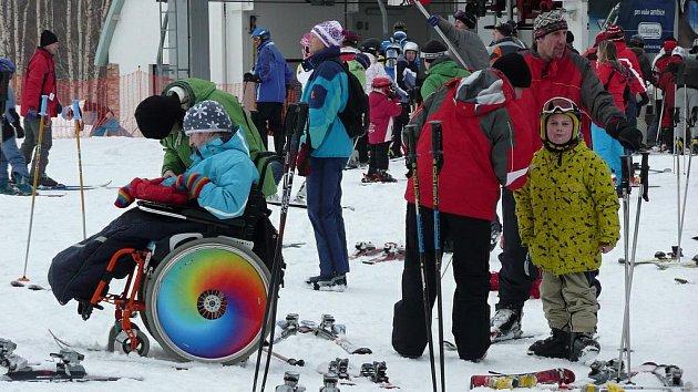 Handicapovaní lyžaři na sjezdovce.