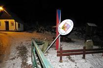 Poškozené zábradlí a značka v Bartošovicích v Orlických horách.