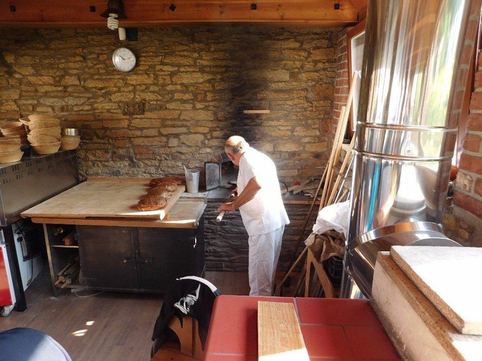 Josef Duben vytahuje voňavý chléb z pece.