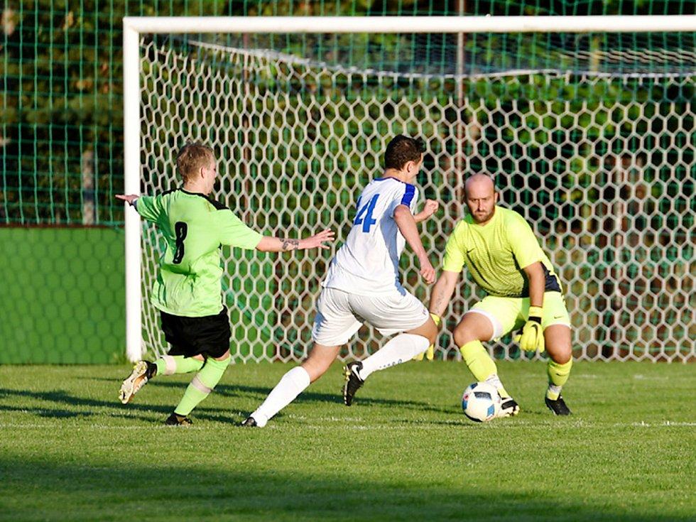 Kostelecký útočník Roman Zajíček (v bílém) běží proti gólmanovi Dobrušky Jaroslavu Klofandovi. V zápase 5. kola krajského přeboru vyhrál Kostelec nad Orlicí 4:0.