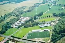 Letecký pohled na areál městského stadionu v Dobrušce. V popředí je vidět nové hřiště s umělou trávou.