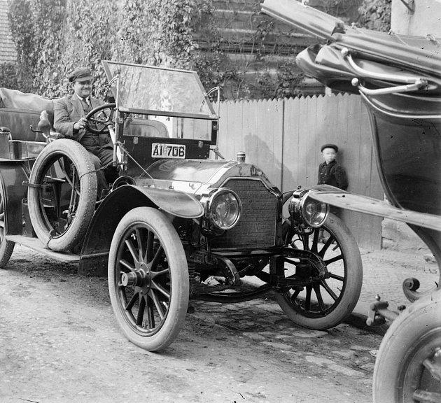 Zavzpomínejte, včem lidé jezdili vKostelci nad Orlicí vminulém století. Na snímku se nachází starý automobil před místním hostincem, období první republiky 1918-1938.