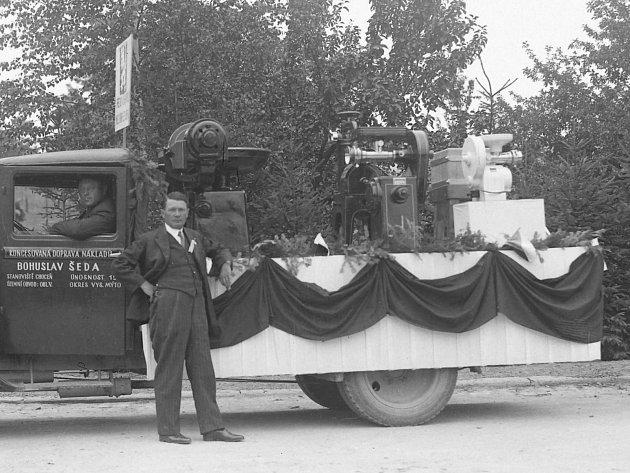 Nákladní vůz pana Bohuslava Šedy zChocně, na automobilu jsou naloženy nějaké stroje (pravděpodobně součást společenského průvodu vKostelci nad Orlicí).