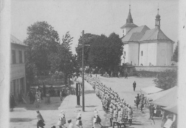 Orelský slet vBystrém roku 1932.Uhřbitovní zdi je trafika, kterou dostal J. Šinták jako válečný invalida, fungovala vletech 1923až 1947.Vlevo před obchodem V. Beneše je benzinová pumpa.