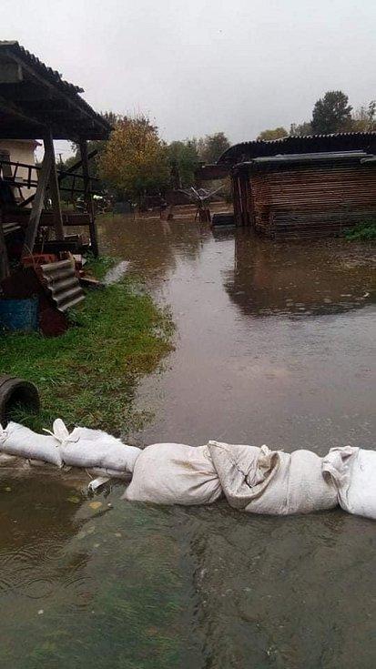 Voda zaplavila zahrady a silnice.