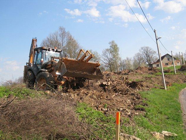 Bagr likviduje kořeny stromů pokácených při stavbě obchvatu Opatova.