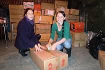 Veronika Svobodová a Mariana Švejcarová při třídění a balení oděvů.