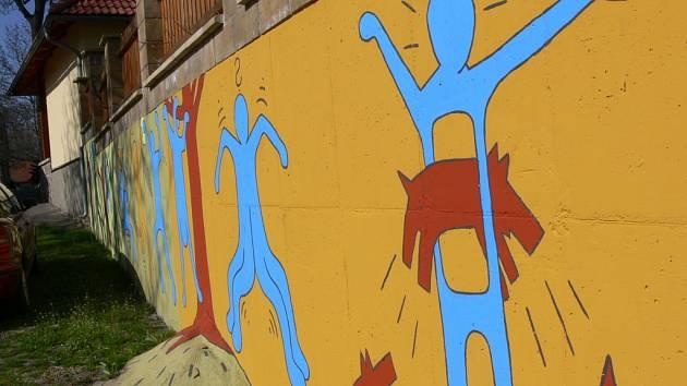 Barevné figury zdobí zeď v centru obce.
