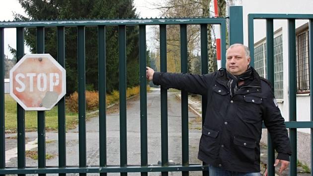 Starosta Květné Petr Škvařil ukazuje u vrátnice, kterým směrem vede vzdálený armádní areál, kde se nachází i muniční sklady. Prostor je střežený.