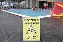 POZOR, V BAZÉNU JE MOKRO!  Cedule v krytém bazénu v Litomyšli upozorňují návštěvníky na kluzkou podlahu. Radní ale přesto tvrdí, že dlažba klouže jako všude jinde.