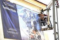 Dělníci umísťují na zeď zámeckého pivovaru v Litomyšli obří plakát, který zve na jedinečnou expozici  Theodora Pištěka.