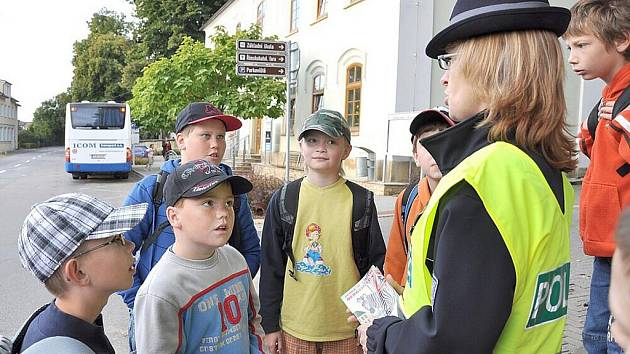 Školáci v Dolním Újezdu si včera zopakovali s policisty zásady správného přecházení silnice.  Ve vesnici u Litomyšle je potřebují, protože denně tu projedou  kolem školy  stovky aut.