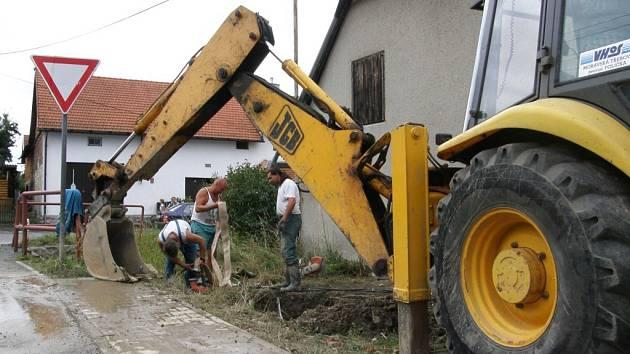 Prasklé potrubí na Družstevní ulici v Poličce bylo ukryté ve dvoumetrové hloubce. Vodohospodáři museli nejprve vyčerpat vodu z jámy, aby mohli opravit přerušené ocelové trubky.
