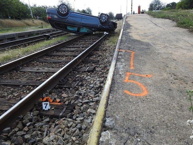 Ujíždějící řidič nakonec auto otočil na střechu poté, co vletěl do kolejiště.