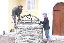 Umělecký kovář Petr Cach osazuje mříž studny.