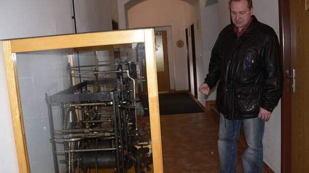 Na chodbě radnice stojí historický hodinový stroj.