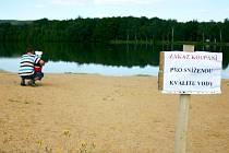 Řasy a sinice plavou po hladině svitavského rybníku Rosnička. Zákaz koupání je pro mnohé návštěvníky pláže nemilým zjištěním.