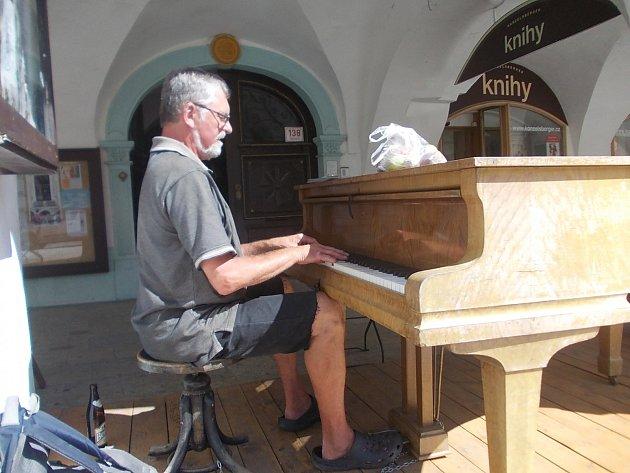 Jiří Michálek hrává na piano u místní kavárny.