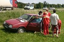 Neporaněná těhotná řidička vystupuje za asistence záchranky z nabouraného vozu.
