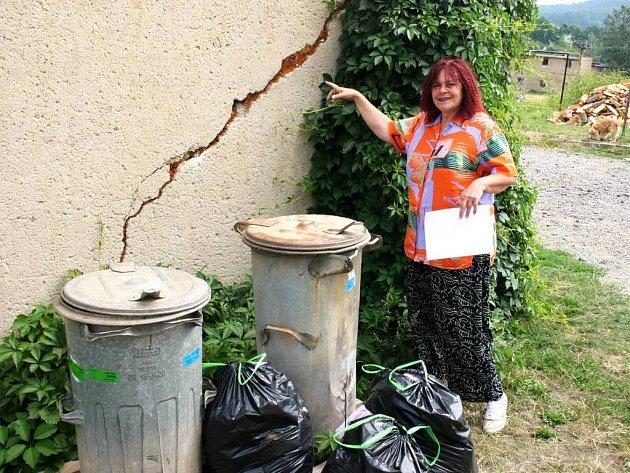 Obyvatelka jednoho z bytových domů Libuše Kozáková ukazuje na praskliny, které způsobila voda tekoucí po rozbité silnici přímo pod dům.