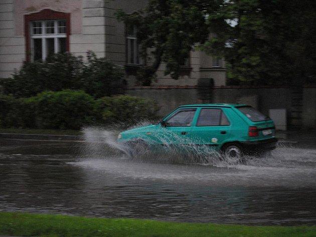 Po průtrži mračen zatopila voda silnici u světelné křižovatky.