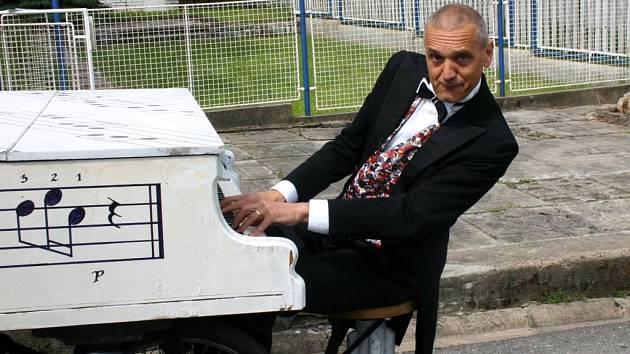 Ulicemi Poličky projíždí s klavírem architekt a herec David Vávra.