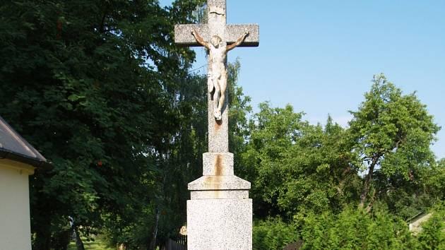 Mezi skromné jubilanty patří i kamenný kříž umístěný hned vedle kapličky  v centrální části Nového Dvora.