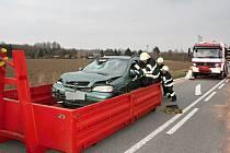 Hasiči odklízejí následky střetu mezi Opelem Astrou a mopedem. Motocyklistu odvážel z místa kolize vrtulník.