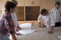 Studenti připravují slavnostní tabuli pod dohledem své učitelky Marie Škaroupkové.
