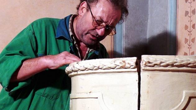 KAMNÁŘ  MAROŠ  GYULA  z Hradce nad Svitavou opravuje kachlová kamna na zámku v Litomyšli.  Pracuje podle dochovaných fotografií a kreseb.