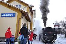 Vlakové nádraží s parní lokomotivou během mikulášské nadílky.