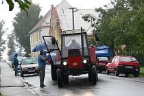 Sám starosta radí traktoristovy jak se vypořádat s uzkým průjezdem mezi zaparkovanými auty.