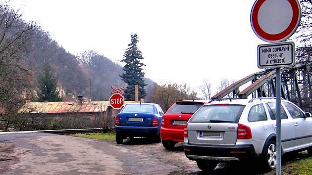 Několik vozidel stálo před železničním přejezdem. Více jich ale parkovalo na trávě za ním!