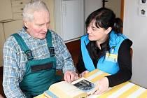 Asistentka ze Spokojeného domova pomáhá klientovi se čtením.