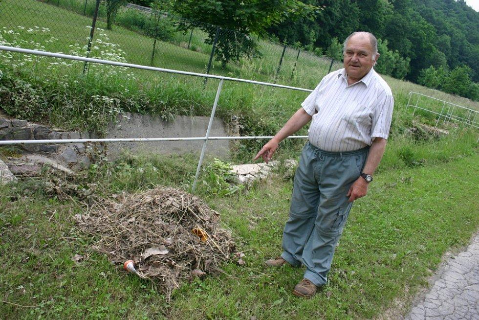 HROMADU trávy, která ucpala při dešti mříže na vpustích do kanálu, ukazuje Josef Měšťák.