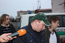 Žháře z KIatusic (v zelené čepici) převážejí policisté na psychiatrické vyšetření.