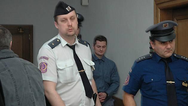 S pouty na rukou přivedla eskorta pouze Jaroslava Rozmana mladšího.