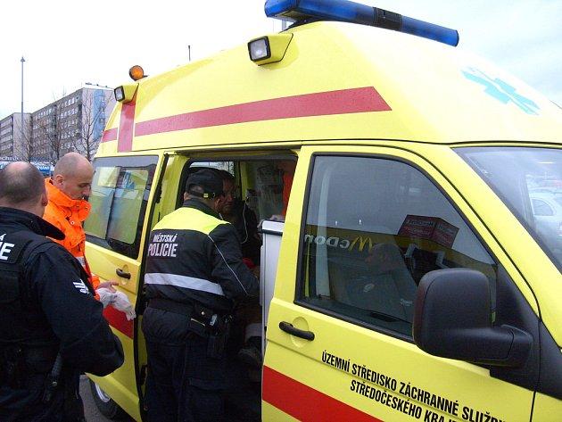 Strážníci pomahájí naložit záchranářům zraněného muže do sanitky.
